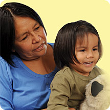 First Nations caregiver holding boy with stuffed toy
